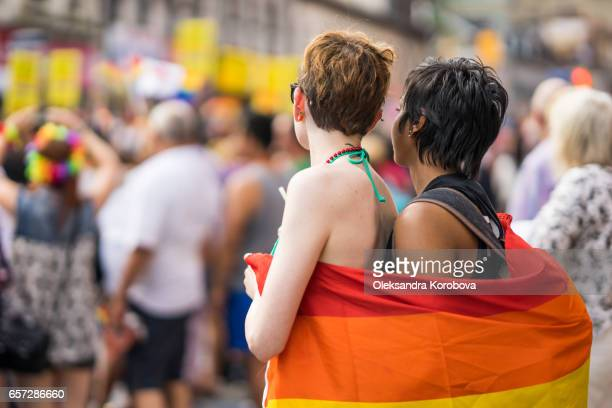 toronto, ontario, canada - july 3, 2016. young mixed-race couple in a crowd celebrating pride parade. wearing colorful rainbow accessories. supporting marriage equality and lgbt rights. - istock photos et images de collection