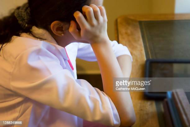 young mixed-race female doctor wearing pink medical scrubs & white lab coat resting head in hand at desk - bad student stock pictures, royalty-free photos & images