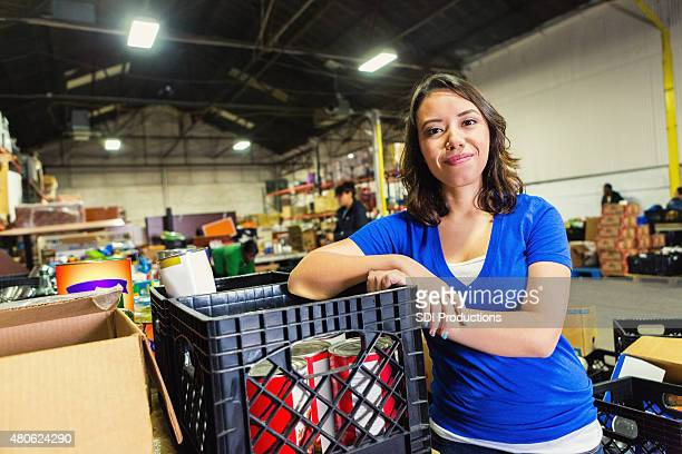 young mixed-race woman volunteering in food bank warehouse - humanitarian aid stock pictures, royalty-free photos & images