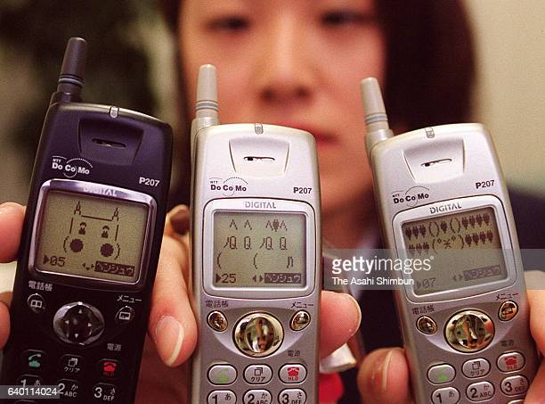 Young mobile phone users show their screen which are full of ASCII art and emoji on February 18 1999 in Nagoya Aichi Japan