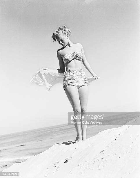 Young model Fran Cooper wearing a patterned bikini on the beach 1948