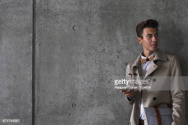 Young Model Holding Mobile While Standing Against Wall