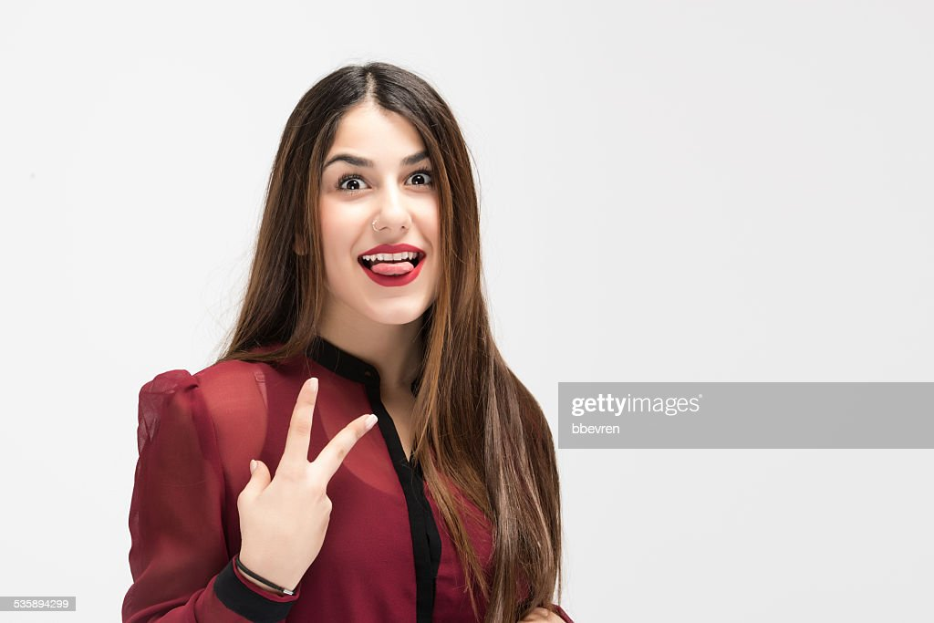 Young model showing v sign with tonque out : Stock Photo