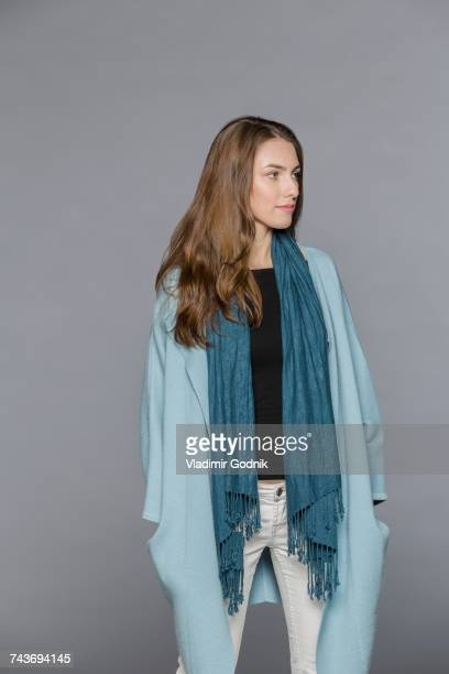 Young model wearing scarf standing with hands in pockets against gray background
