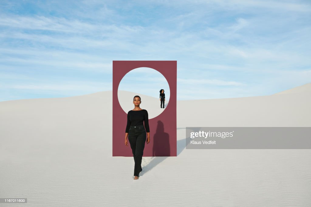 Young models with portal standing at desert against sky : Stock Photo