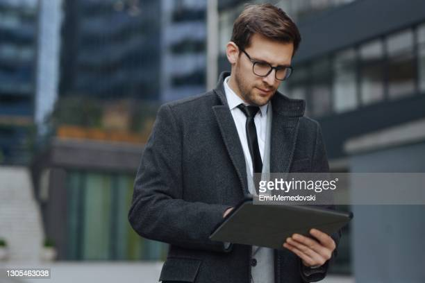 young modern executive using tablet outdoors - businesswear stock pictures, royalty-free photos & images
