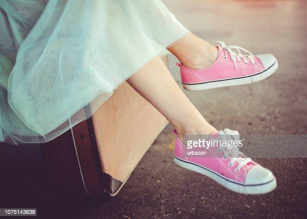 a young modern girl sitting and waiting for a train. - canvas shoe stock pictures, royalty-free photos & images