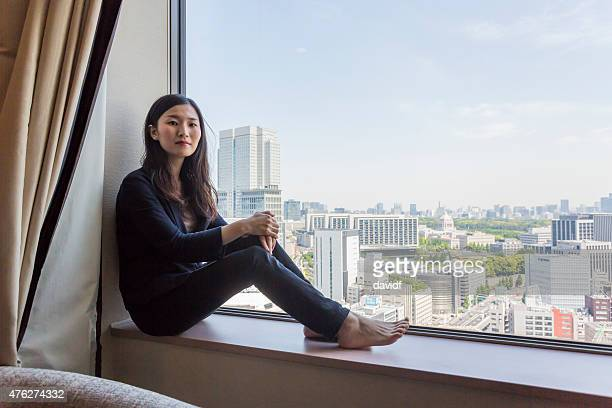 Young modern Japanese woman sitting looking at the view