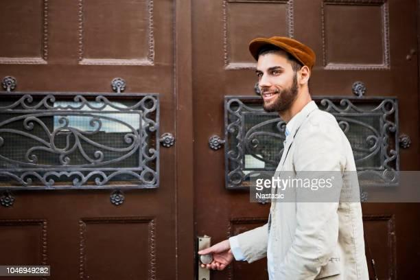 moderne jongeman voor oude stijlvolle houten deur - baret stockfoto's en -beelden