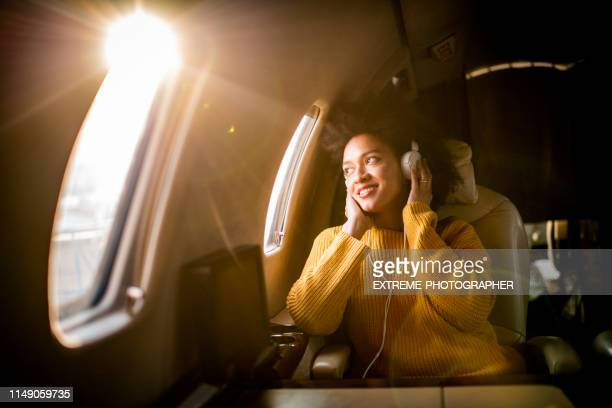 young modern woman sitting in a private jet, listening to music through the headphones and looking through the window - vip stock pictures, royalty-free photos & images