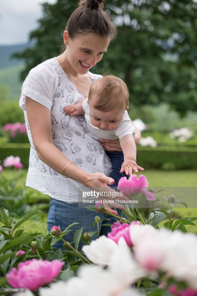 miguel pedomom gif boys 29  mom boy Young mom and baby boy admiring and smelling flowers outside in  garden : ストック