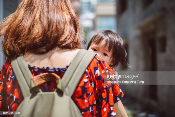 Young mom carrying baby while baby looking over mom's shoulder.