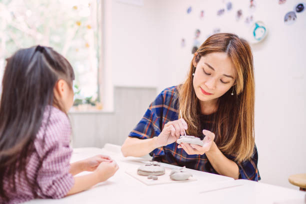 Young mom & daughter making decorative pottery plates in workshop joyfully