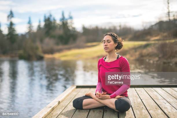Young mom doing yoga outside by lake