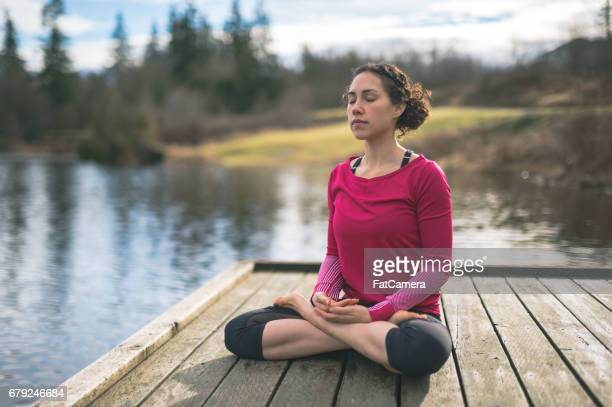Young mom doing yoga outside by lake