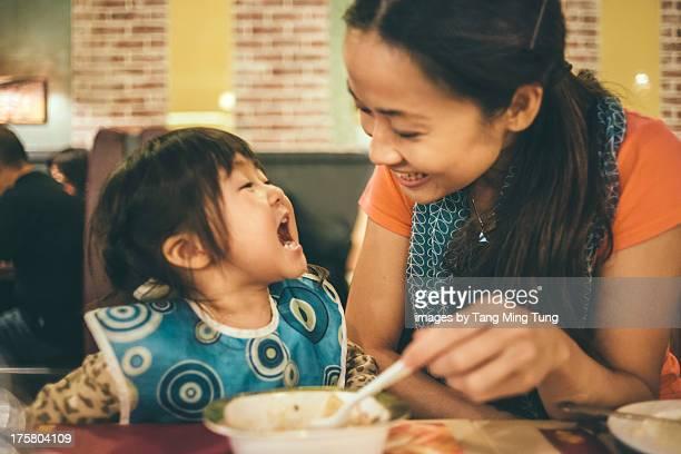 Young mom feeding toddler in restaurant joyfully