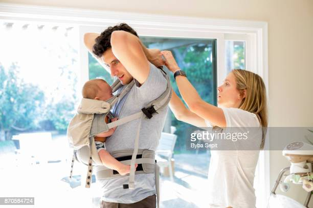 Young mom helping young father to harness a baby