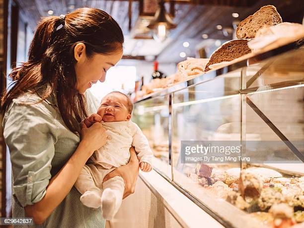 Young mom holding baby at bakery