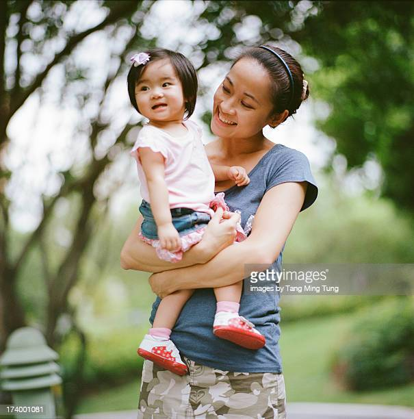 Young mom holding baby in park with love
