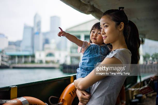 Young mom holding & talking to toddler on a ferry
