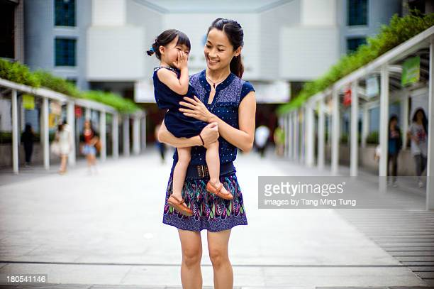 Young mom holding toddler in her arms joyfully.