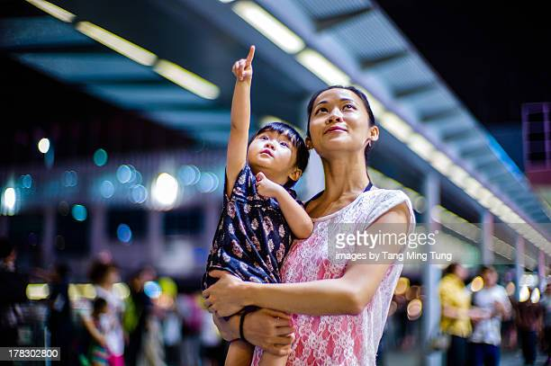 Young mom holding toddler on street at night