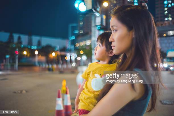 Young mom holding toddler waiting to cross a road