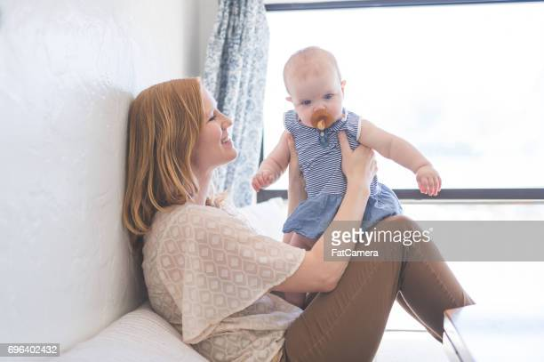 young mom holds and smiles with her baby girl - fat women in bath stock pictures, royalty-free photos & images