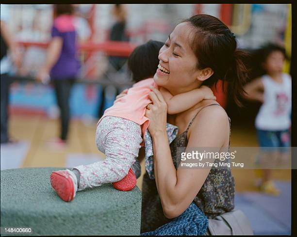 Young mom hugging her baby joyfully in playground