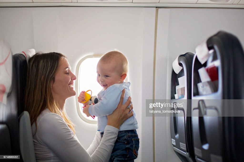 Young mom, playing and breastfeeding her toddler boy on board of aircraft : Stock Photo