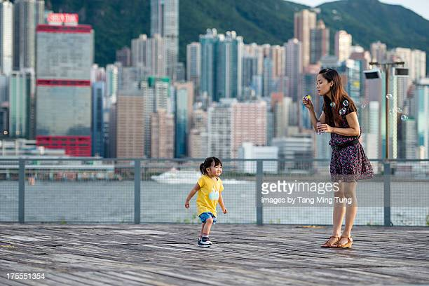 Young mom playing bubbles with toddler girl
