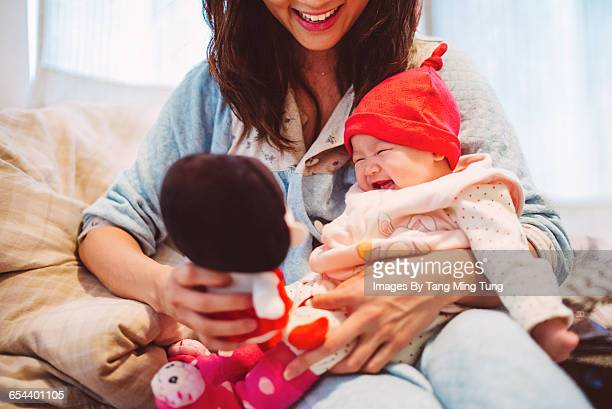 Young mom playing with baby joyfully on bed