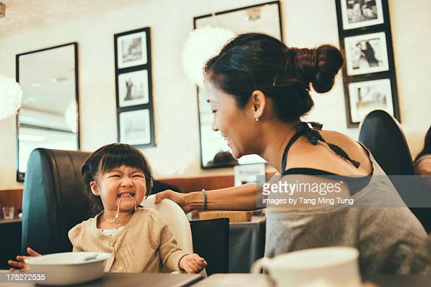 Young mom playing with toddler on dining table