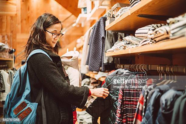 Young mom shopping kids wear with her little baby