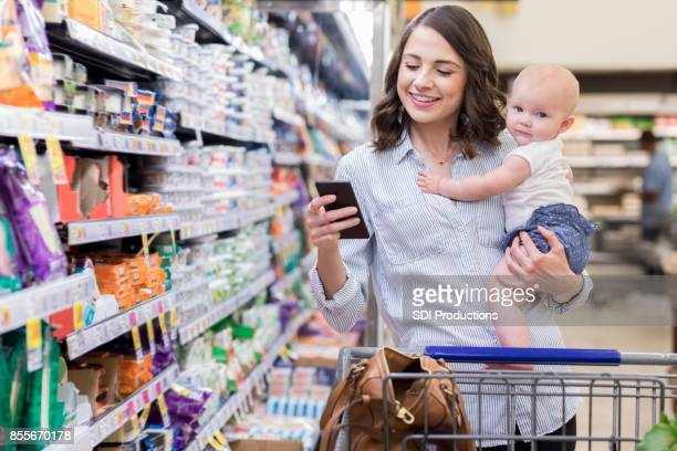 young mom shops with her baby in supermarket - grocery shopping stock photos and pictures