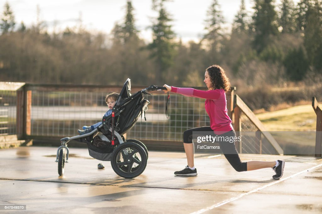 Young mom stretching next to child in baby stroller : Stock Photo