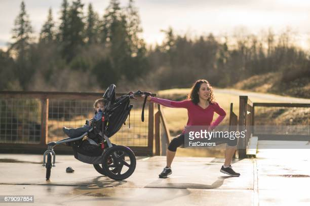 Young mom stretching next to child in baby stroller