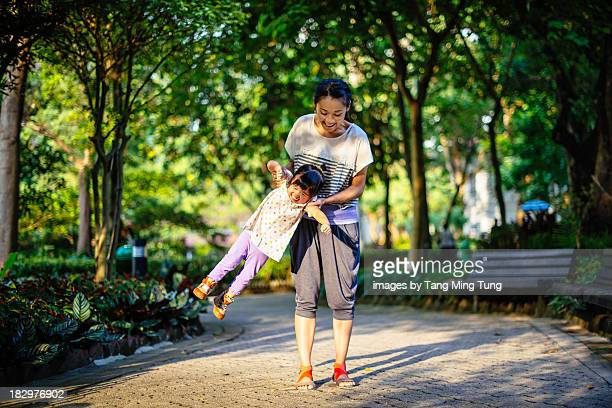 Young mom swinging toddler girl in a park joyfully