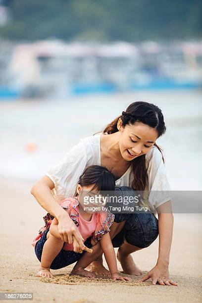 Young mom & toddler girl playing sand on beach