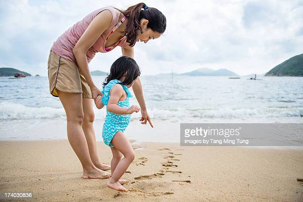 Young mom & toddler having fun at beach
