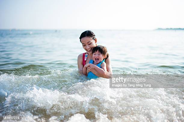 Young mom & toddler swimming in the sea joyfully 1