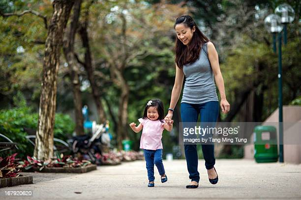 Young mom & toddler walking and dancing in park