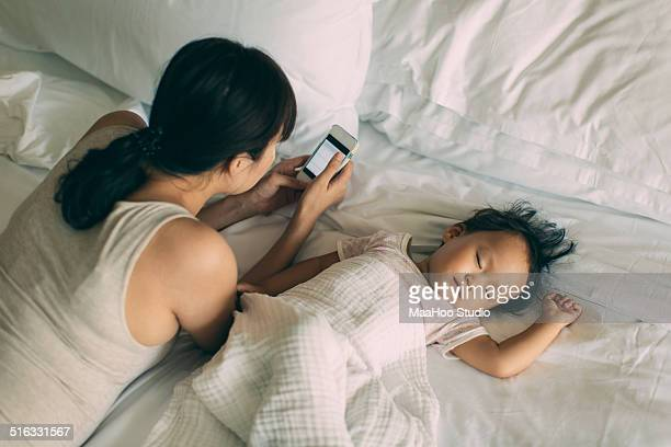 Young Mom uses smartphone with a sleeping baby