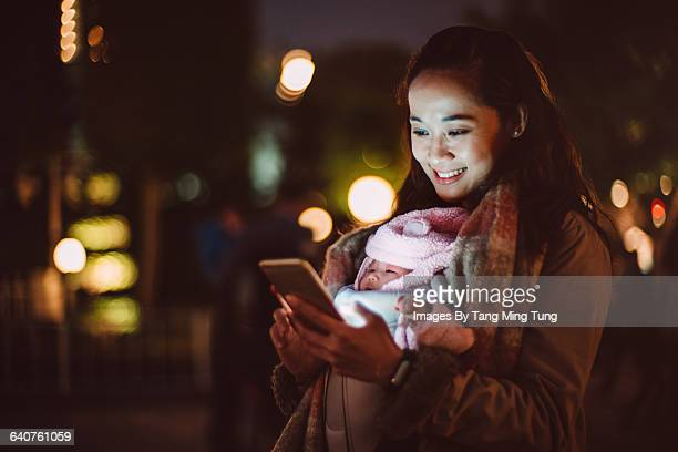 Young mom using smartphone at night