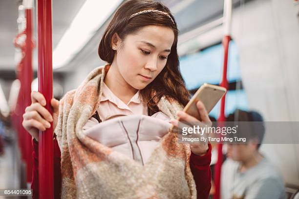 Young mom using smartphone on train