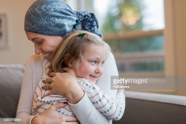 young mom with cancer holds her daughter tightly - cancer illness stock pictures, royalty-free photos & images