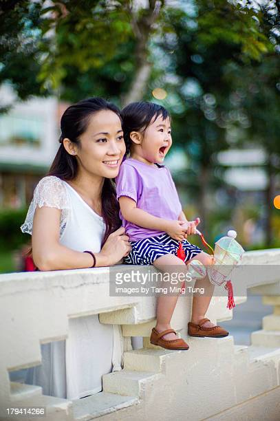 Young mom with toddler holding chinese lantern