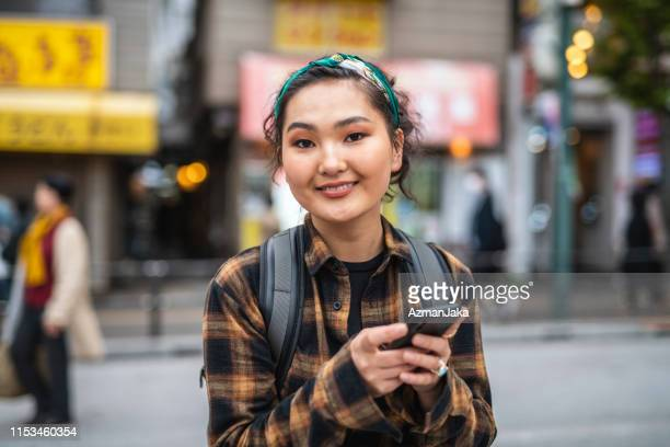 young mongolian female traveler texting in tokyo - mongolian women stock photos and pictures