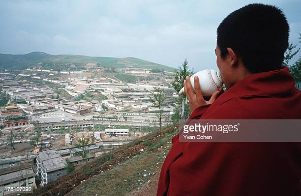 A young monk blows into a conch shell in a ritual call to prayer on a hill overlooking Kumbum monastery close to Xining Kumbum monastery is believed...