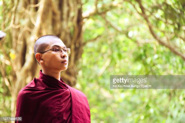 young monk looking away against trees - ko ko htike aung stock pictures, royalty-free photos & images